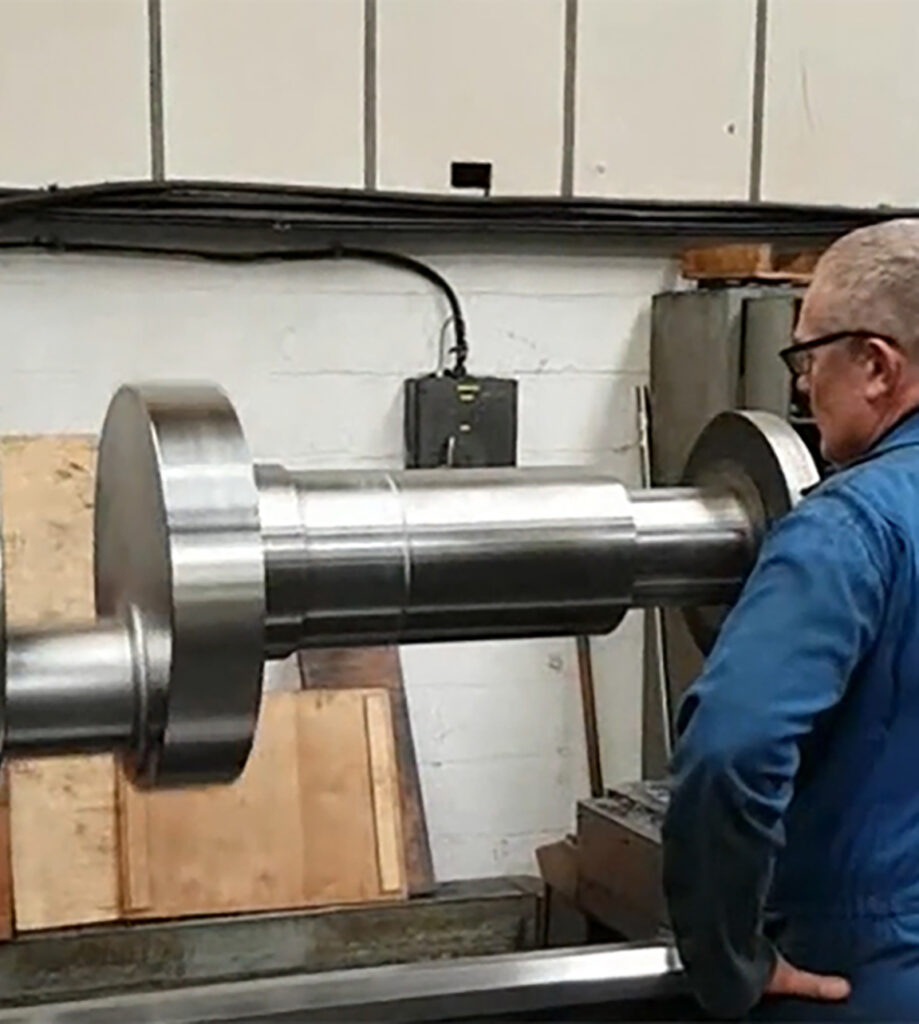 Male worker looking at large crank shaft header.